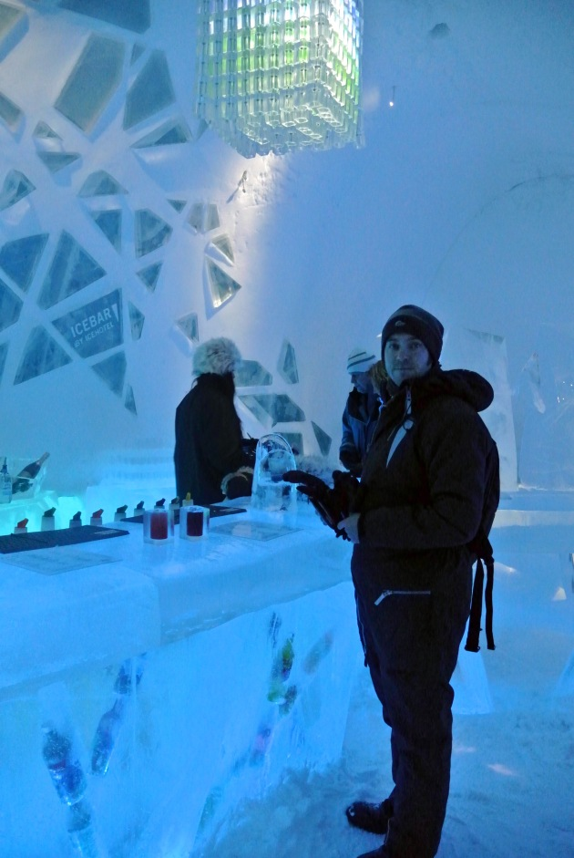 My partner standing at the ICEBAR under the Chandelier made of ICEBAR glasses (over 200)